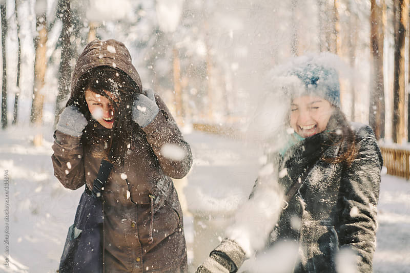 Two joyful girlfriends having fun in the snow during a cold winter day by Borislav Zhuykov for Stocksy United