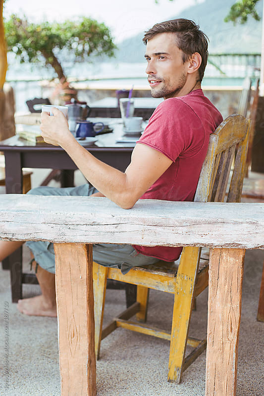 Relaxing - man drinking his coffee in a wooden cafe shop by Jovo Jovanovic for Stocksy United
