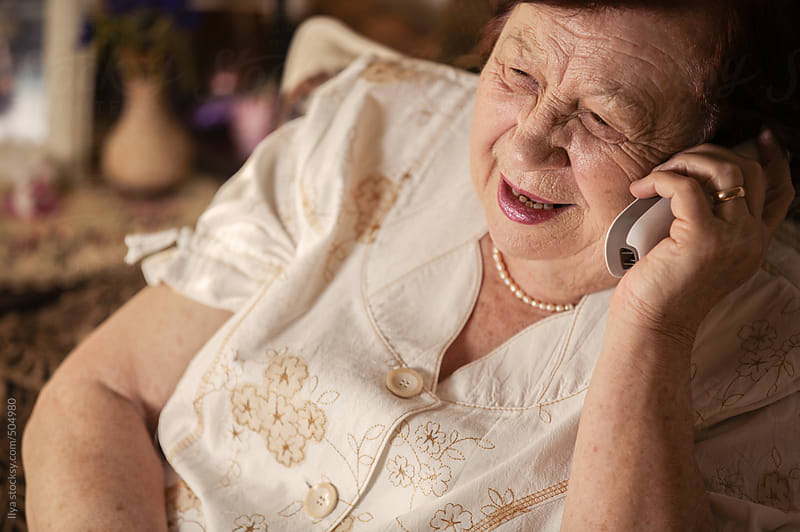 Happy senior woman talking on cellphone smiling by Ilya for Stocksy United
