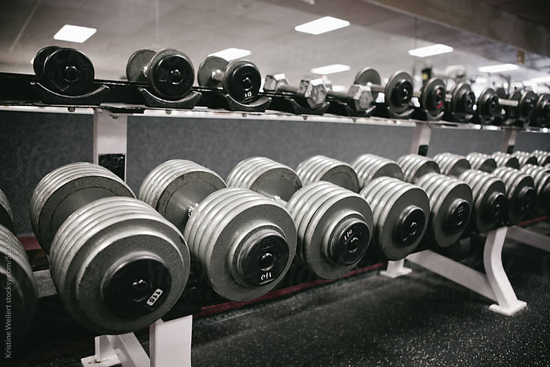 Lined up dumbless in a gym environment by Kristine Weilert for Stocksy United