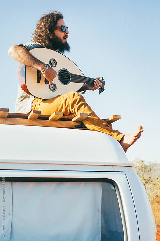 Cool Bearded Young Man Sitting on Roof of White Camper Van and Playing Oud (Mandolin) by Julien L. Balmer for Stocksy United