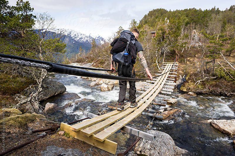 man crossing a river on a suspension bridge while hiking in Norway. by Tristan Kwant for Stocksy United