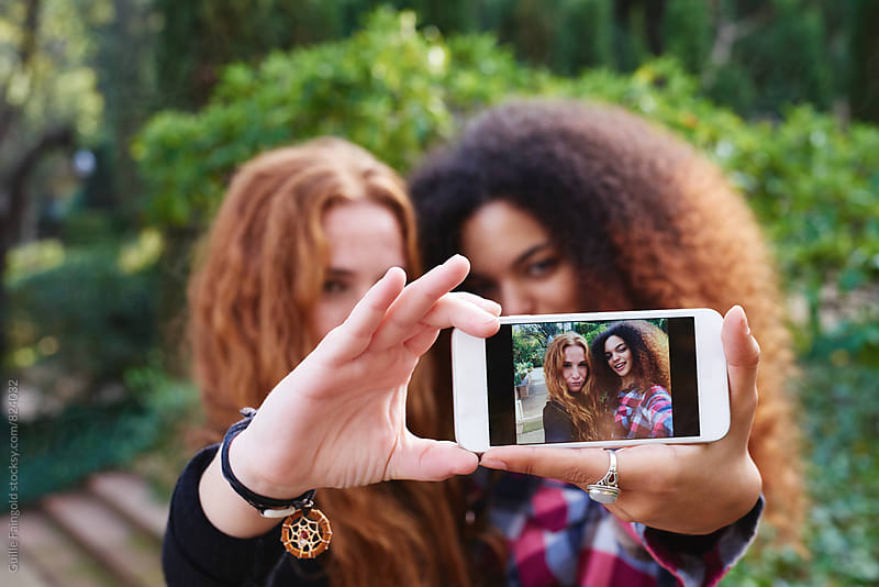 Two young women taking selfie outdoors by Guille Faingold for Stocksy United