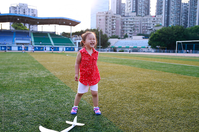 happy little girl outdoor in football field by cuiyan Liu for Stocksy United