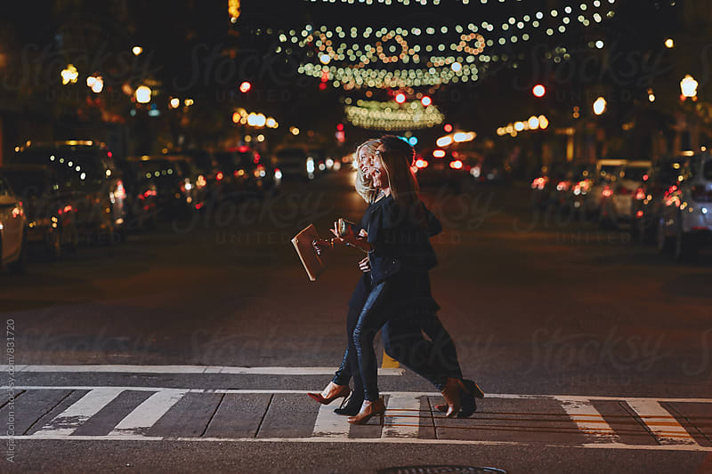 Cute women crossing the street at night by Alicja Colon for Stocksy United