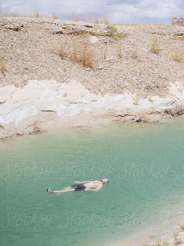 Young guy floating in green water in a desert setting in utah by Jeremy Pawlowski for Stocksy United