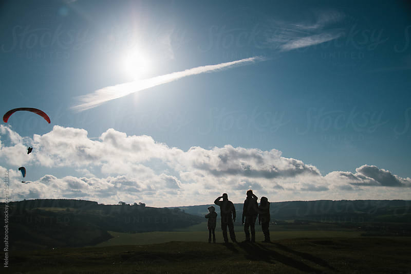 A family group, in silhouette, watching paragliders from the top of a hill by Helen Rushbrook for Stocksy United