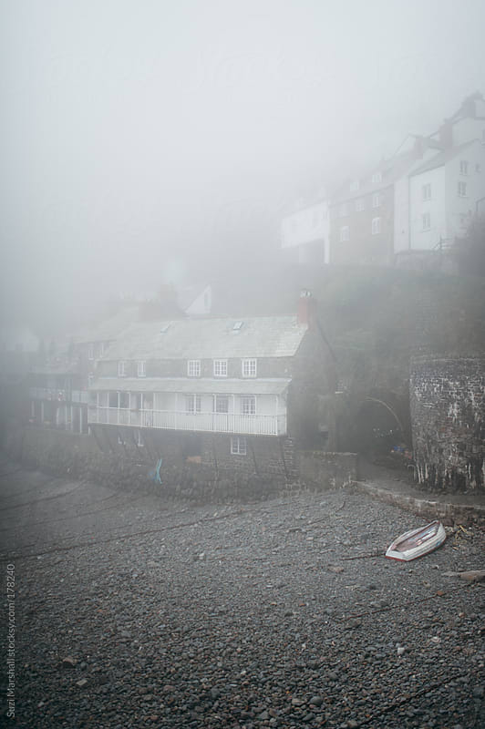 Fishing village and harbour shrouded in fog by Suzi Marshall for Stocksy United
