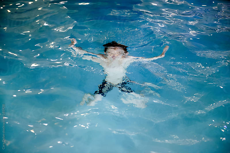 Boy is underwater in a pool at night by Cara Dolan for Stocksy United