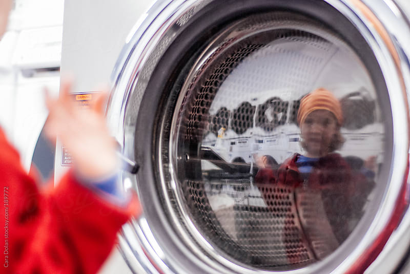 Boy looks at himself in the reflection of a dryer at a laundromat by Cara Dolan for Stocksy United