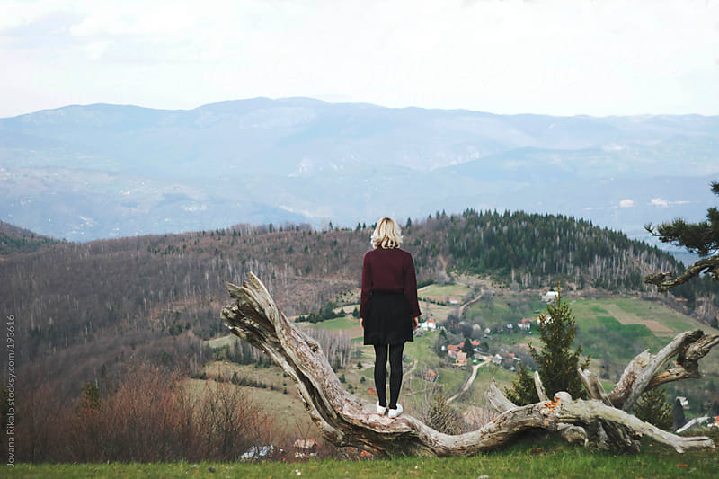 Young woman standing on a big branch and enjoy the view by Jovana Rikalo for Stocksy United