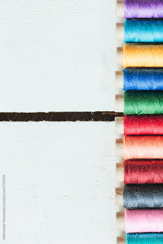 Arrangement of colorful threads against white wooden background by Aleksandar Novoselski for Stocksy United