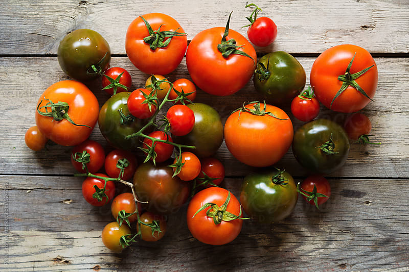 Various tomatoes on wooden table by Pixel Stories for Stocksy United