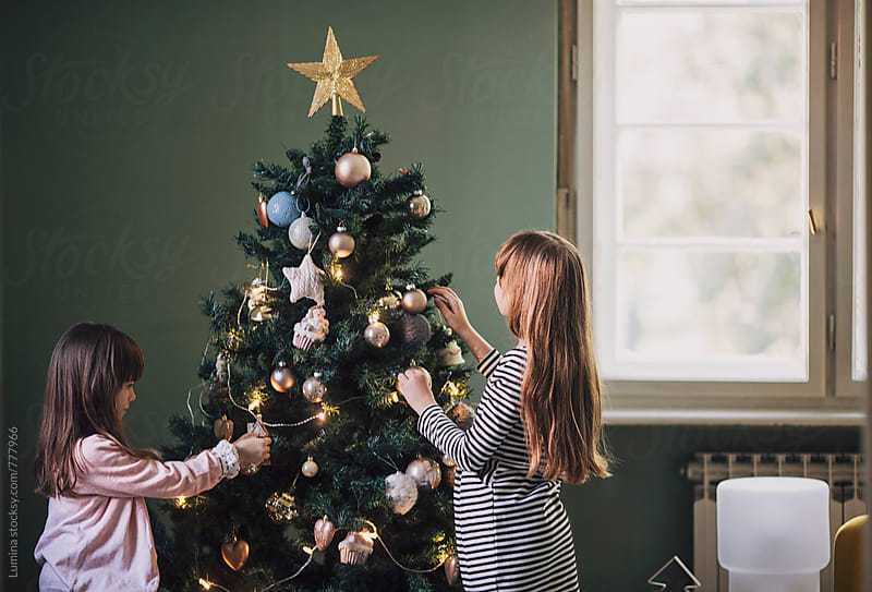 Sisters Decorate the Christmas Tree by Lumina for Stocksy United