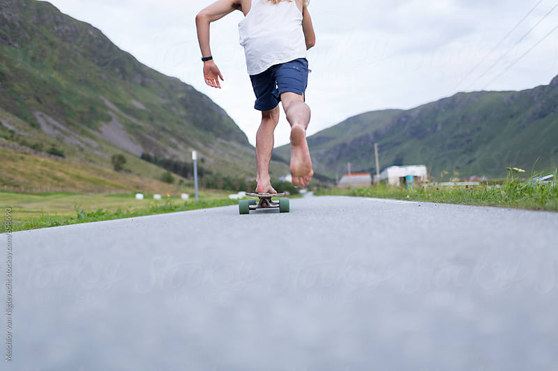 Young man takes off on his skateboard on the road by Melchior van Nigtevecht for Stocksy United