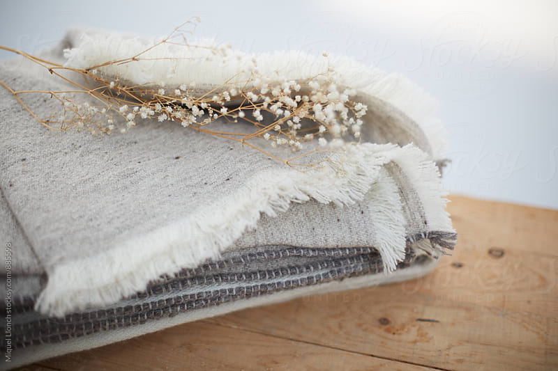 Stack of wool blankets with dry flowers on a table by Miquel Llonch for Stocksy United
