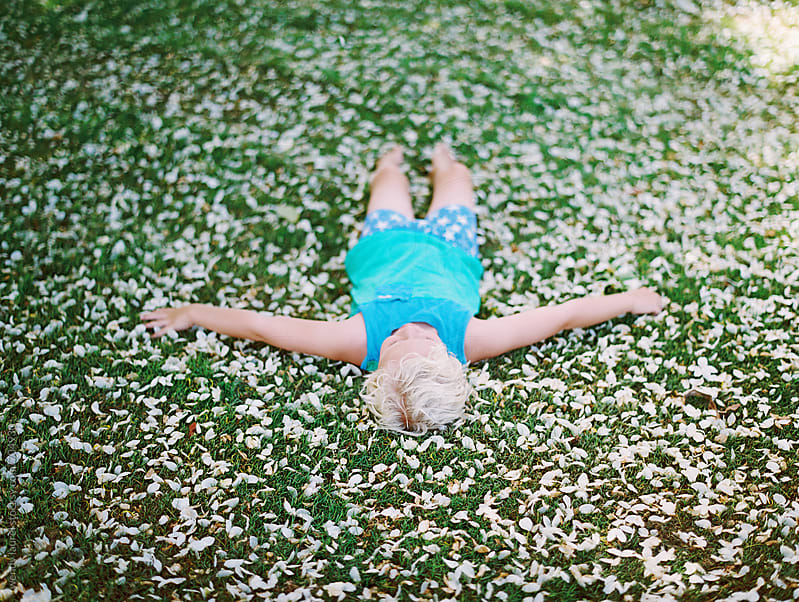 little boy in blue tank top and pjs and laying on bed of flower petals on green grass by wendy laurel for Stocksy United