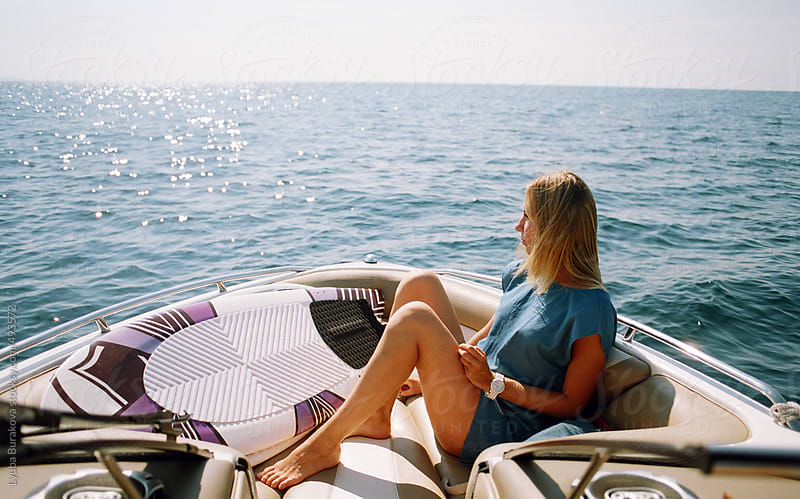 Young woman relaxing in the motorboat with wakeboard  by Lyuba Burakova for Stocksy United