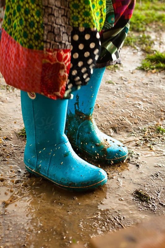 Person wearing rubber boots standing in a mud. by Mosuno for Stocksy United