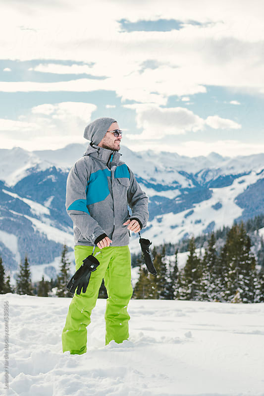 young casual man in colorful skiing pants standing in snowcovered mountain landscape by Leander Nardin for Stocksy United