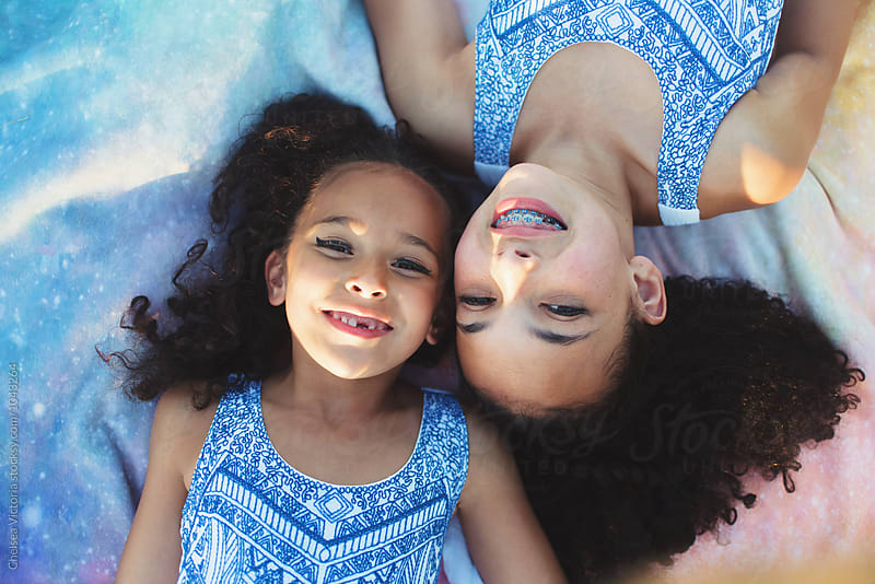 Young sisters laying on a blanket by Chelsea Victoria for Stocksy United