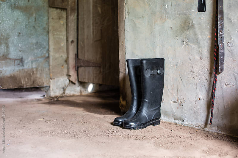 Wet weather boots on a dirt floor by Jacqui Miller for Stocksy United