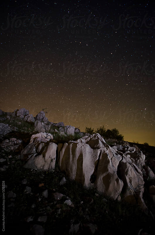 Night photo with starry sky and cliffs at the mountain by Cosma Andrei for Stocksy United