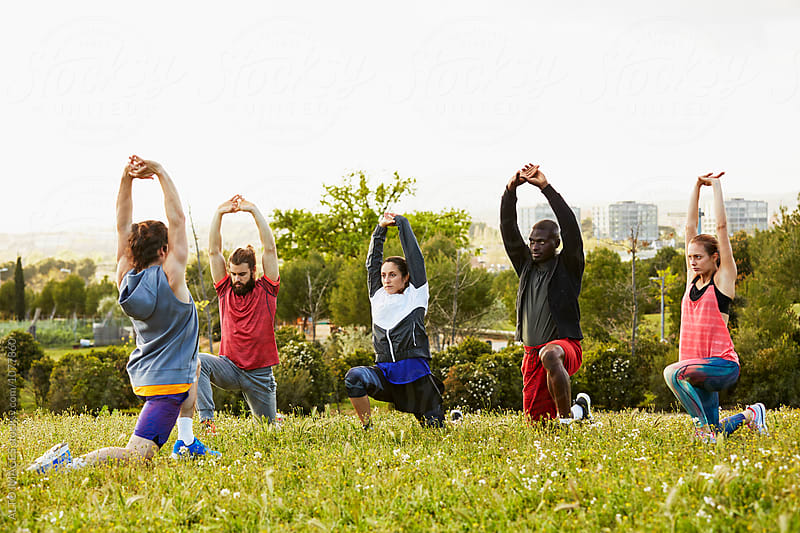 Athletes Stretching With Arms Raised In Park by ALTO IMAGES for Stocksy United