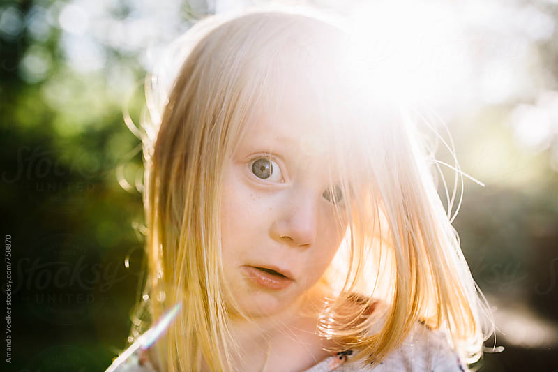 Little Girl Making Silly Wide Eyed Face With Sunflare by Amanda Voelker for Stocksy United