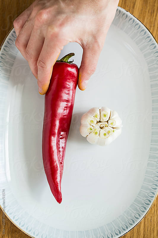 hand placing red pepper on vintage plate next to garlic by Lior + Lone for Stocksy United