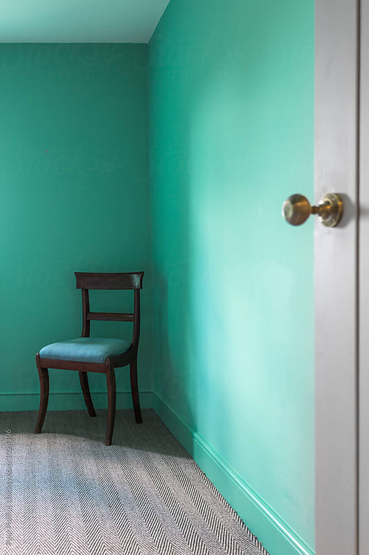 Chair in the corner of a green  room. by Paul Phillips for Stocksy United