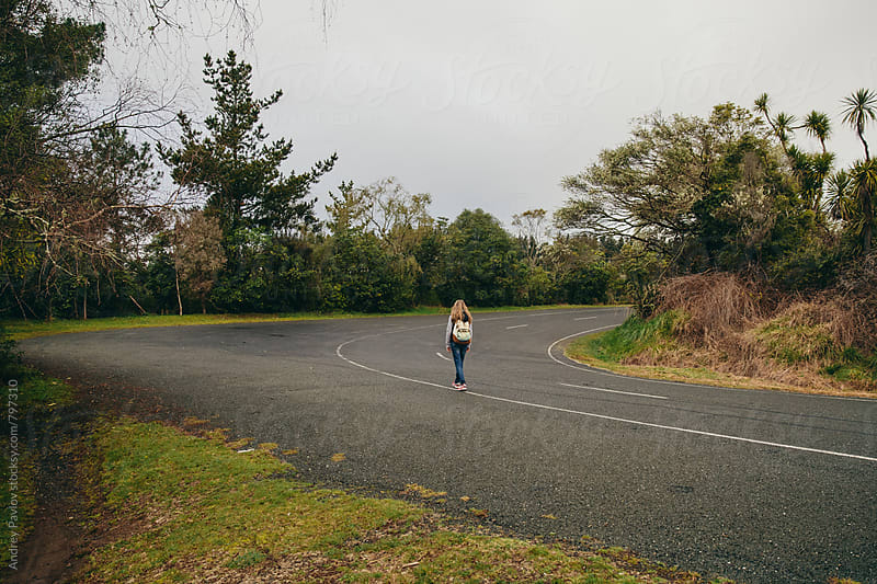 Woman walking alone on the road by Andrey Pavlov for Stocksy United