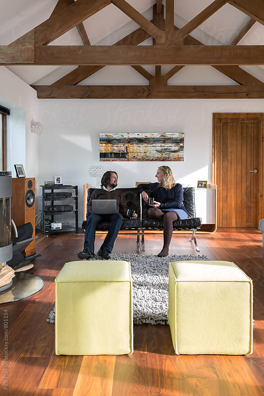 Couple talking seated in a contemporary living room. by Paul Phillips for Stocksy United