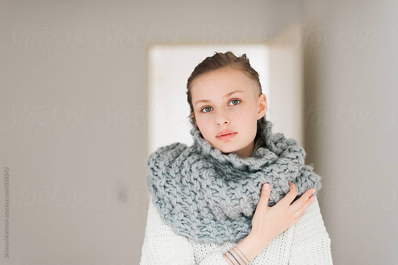 Young Fashionable Woman Wearing a Warm Scarf and Sweater Indoors by Briana Morrison for Stocksy United