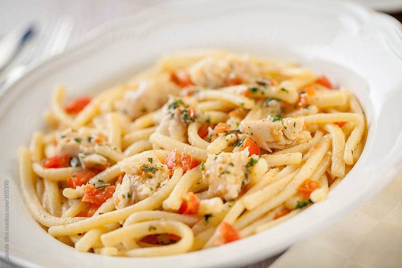 Pasta with fresh tomatoes and cod by Davide Illini for Stocksy United