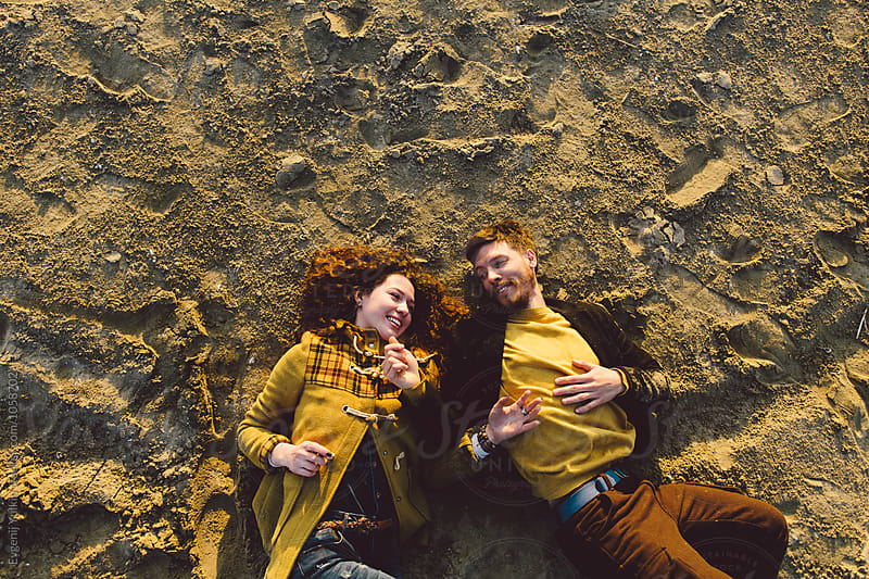 Young couple looking to each other laying on the sand by Evgenij Yulkin for Stocksy United