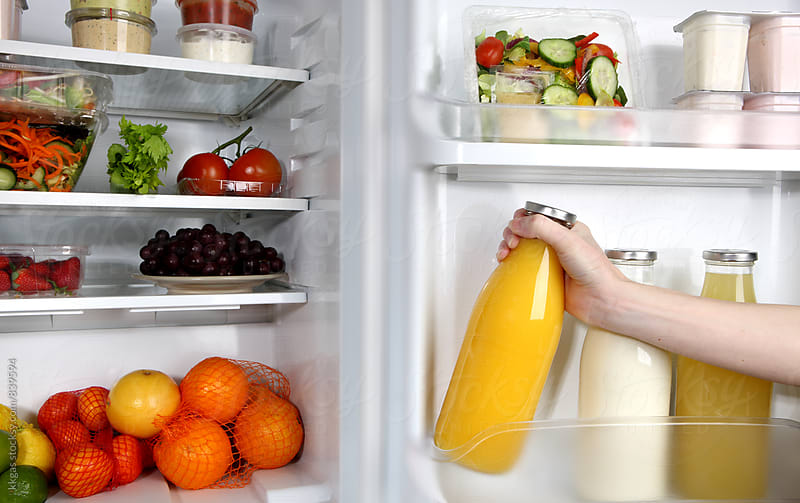 Woman taking orange juice form a full refigerator, by kkgas for Stocksy United