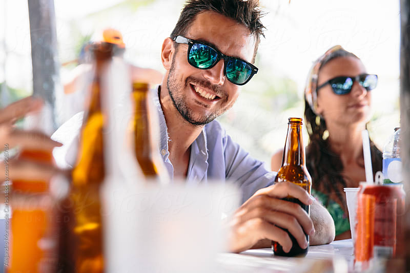 Handsome man in mirrored sunglasses with bottle of beer by Alejandro Moreno de Carlos for Stocksy United