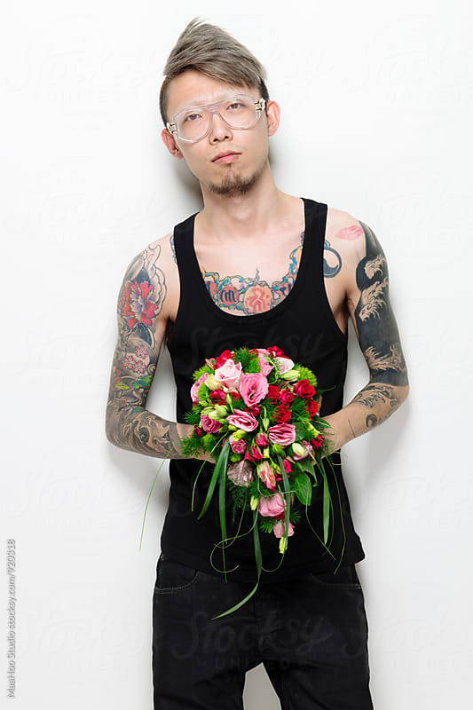 Portrait of man with tattoo holding a bunch of flower by Maa Hoo for Stocksy United