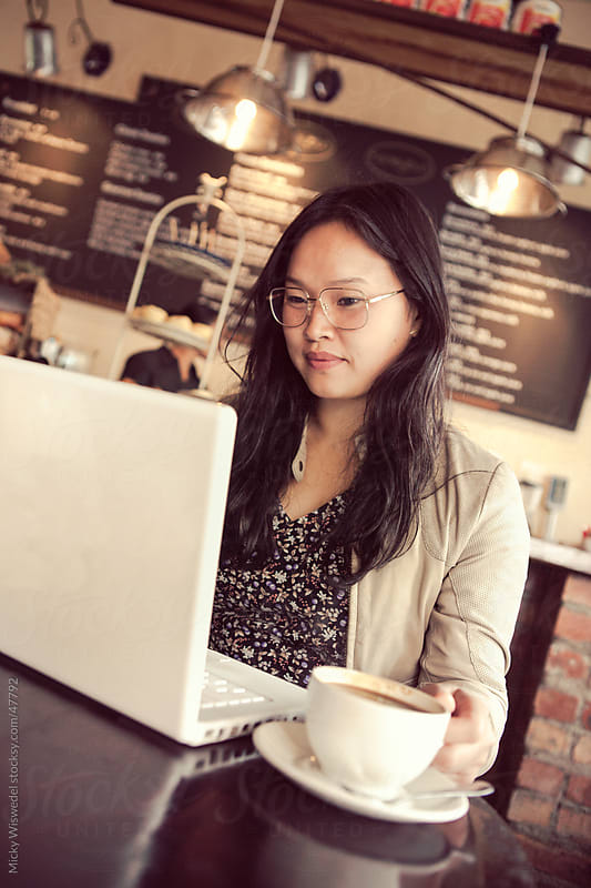 Young Asian woman working on her laptop in a coffee shop by Micky Wiswedel for Stocksy United