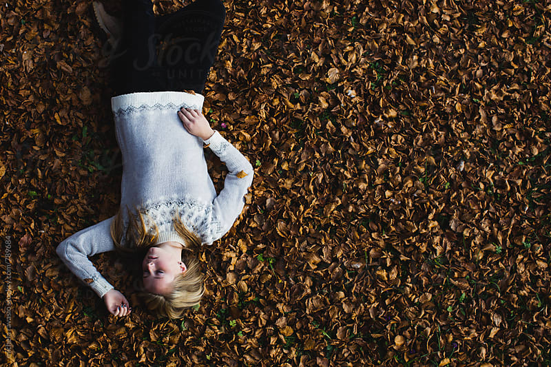 Young girl on a bed of dry leaves by michela ravasio for Stocksy United