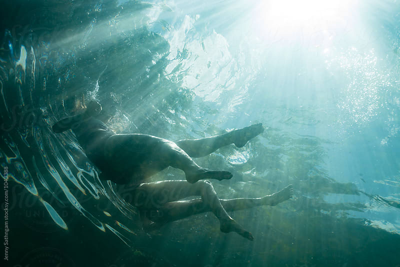 Two women swimming in clear water by Jenny Sathngam for Stocksy United