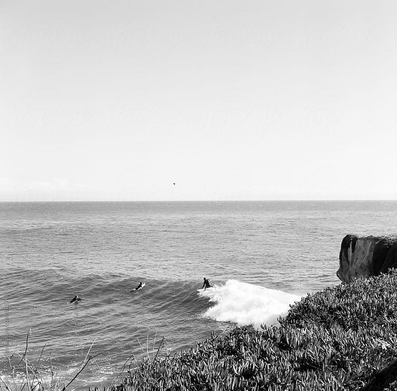 Surfers and cliff break at Steamers Lane in Santa Cruz by Briana Morrison for Stocksy United
