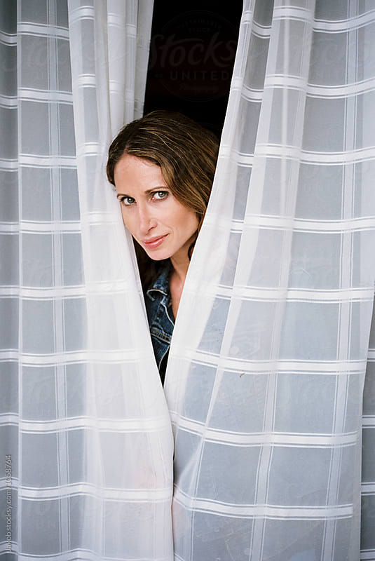 Beautiful woman peeking out behind two window drapes by Jakob for Stocksy United
