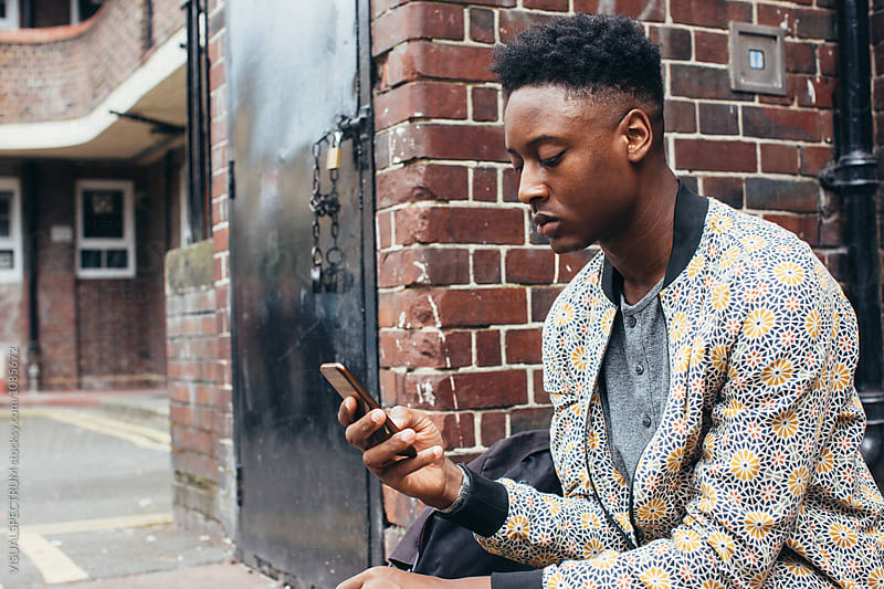 Young Black Man Sitting in Front of Typical London Home and Using Cellphone by VISUALSPECTRUM for Stocksy United