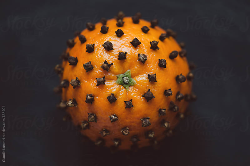 Orange pierced with cloves, close-up by Claudia Lommel for Stocksy United