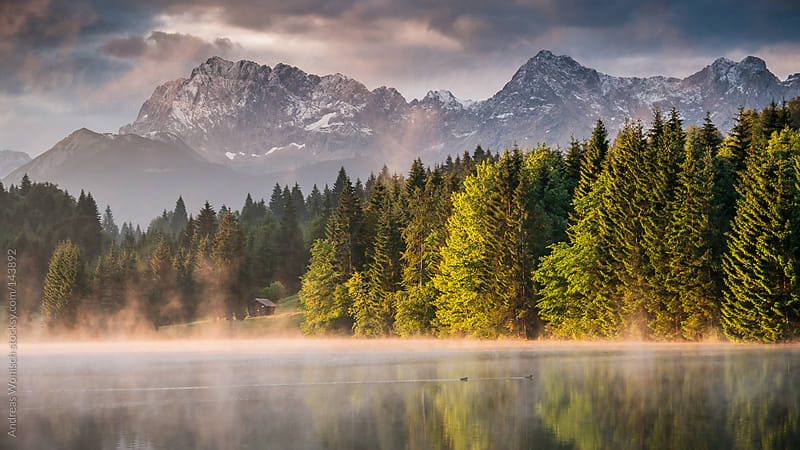 Lake view at Sunrise with Alps in the Background by Andreas Wonisch for Stocksy United