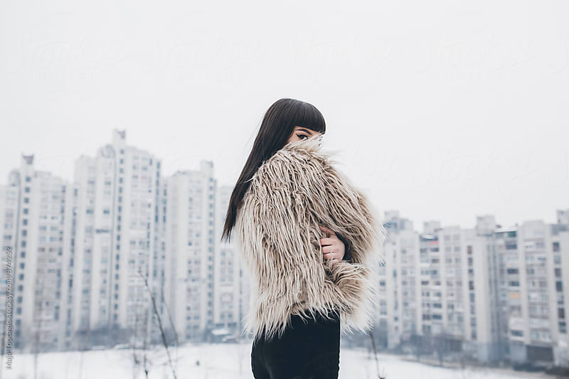 Beautiful young woman in a fur coat outdoors by Maja Topcagic for Stocksy United