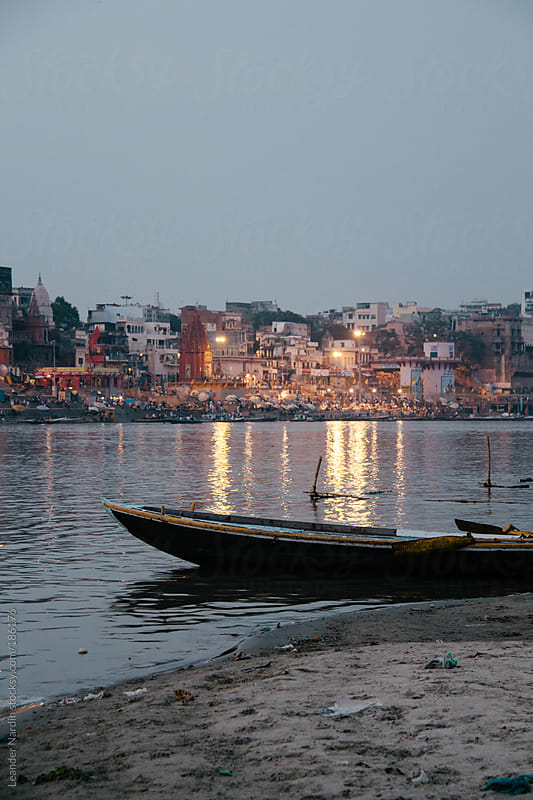 boat on the shore of the ganges with the riverside of varanasi in the back by Leander Nardin for Stocksy United