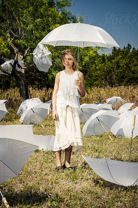 Young Girl with Umbrellas in Field by Geoffrey Hammond for Stocksy United